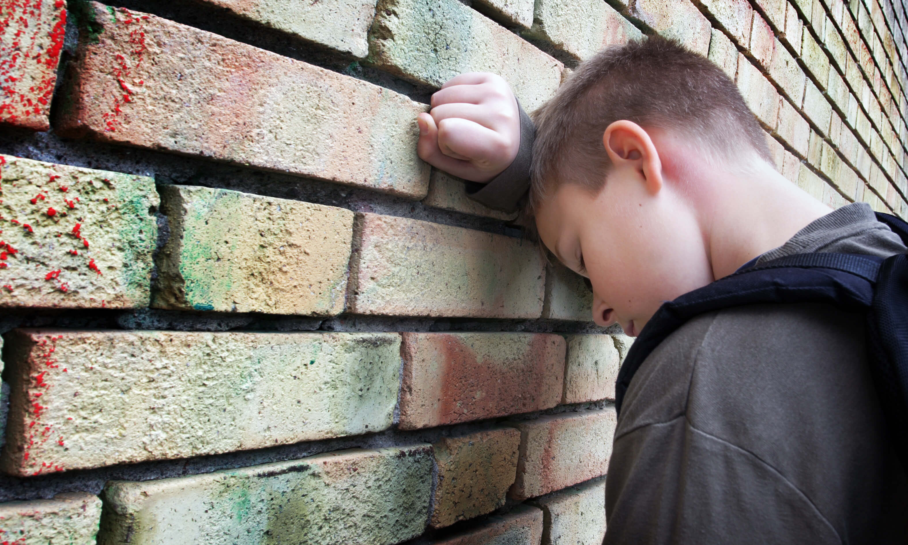 child leaning on a wall